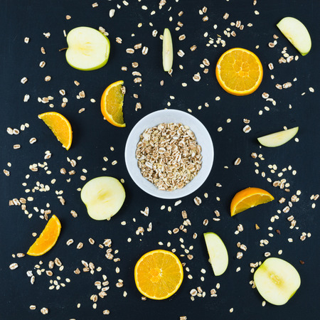 Good morning with healthy breakfast with composition flat lay of sliced apple and orange, oats and whole spelled isolated on blackboard background - top view Stock Photo - 97833510