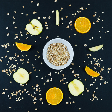 Good morning with healthy breakfast with composition flat lay of sliced apple and orange, oats and whole spelled isolated on blackboard background - top view