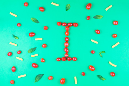 Italian food eating pattern with letter I composed by many red cherry tomatoes, basil leaves and macaroni isolated on green background Stock Photo