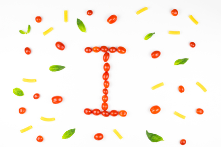 Italian food eating pattern with letter I composed by many red cherry tomatoes, basil leaves and macaroni  isolated on white background Stock Photo