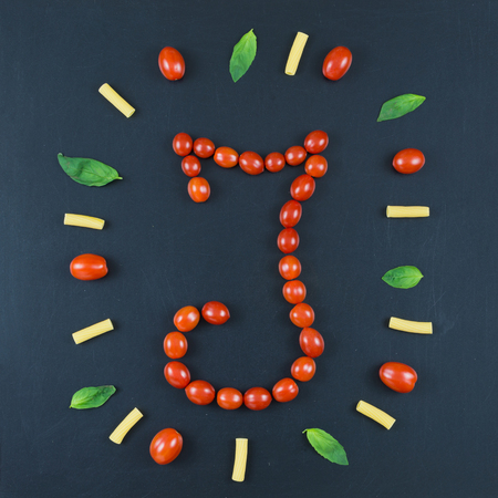 Italian food eating pattern with letter I composed by many red cherry tomatoes, basil leaves and macaroni isolated on blackboard background
