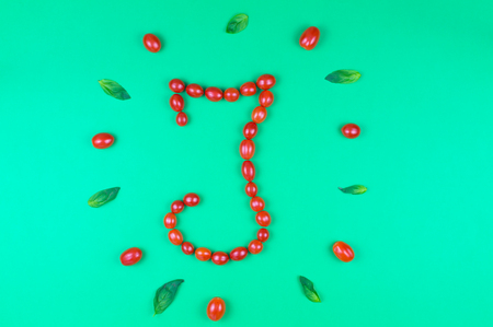 Italian food eating pattern with letter I composed by many red cherry tomatoes and basil leaves isolated on green background