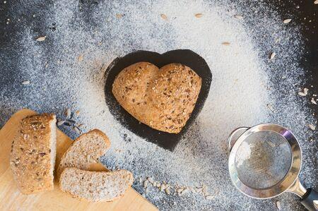 Heart shape of wholemeal bread on blackboard backround