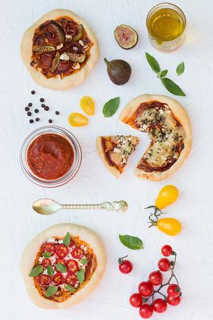 make a paste: Mini Pizzas on white table