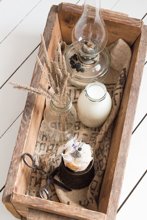 Cookies with Milk, Dried Flowers and an Oil Lamp in a Wooden Box photo