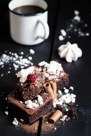 Homemade Double Chocolate Cake with Crushed Meringues, Wafer Rolls, a Ripe Berry on Top and Coffee. Dark Wooden Table Background. Moody Atmosphere photo