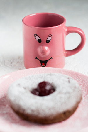 Happy Mug Looking at a Powdered Sugar Donut. Shallow Depth of Field photo