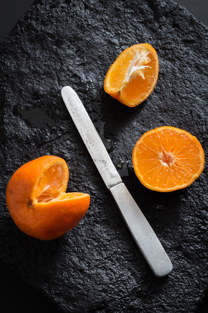 soapstone: Juicy Mandarin Oranges and a Silver Knife on a Black Stone Plate. Overhead View