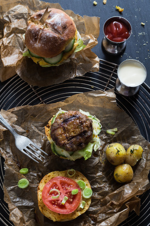 caloric: Homemade Juicy Pork Burger, a Veggie One with a Flag Topper and Buttered Baby Potatoes with Dill Stock Photo