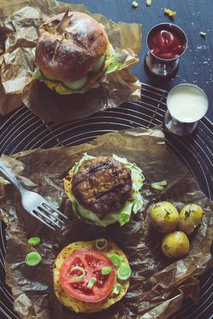 moody background: Retro Filtered Image: Homemade Juicy Pork Burger, a Veggie One with a Flag Topper and Buttered Baby Potatoes with Dill