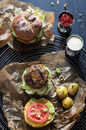 topper: Homemade Juicy Pork Burger, a Veggie One with a Flag Topper and Buttered Baby Potatoes with Dill Stock Photo