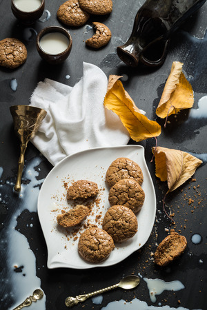 Flourless Walnut Cookies, Milk and Cherry Leaves Messy Still Life photo