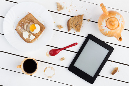 kindle: Eating and EReading. Buttered Toast with a Boiled Egg and Black Coffee Stock Photo