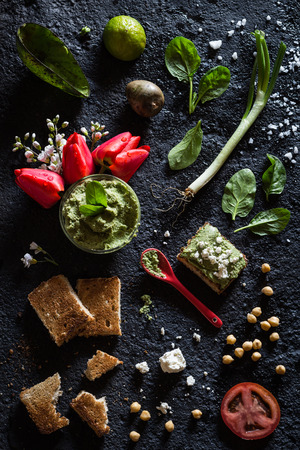 Chickpea Avocado Spinach Green Onion and Feta Cheese Dip on a Toast. Black Concrete Background. Overhead View