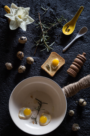 sunnyside: Rosemary SunnySide Up Quail Eggs and a Rusk. Black Concrete Background. Overhead View