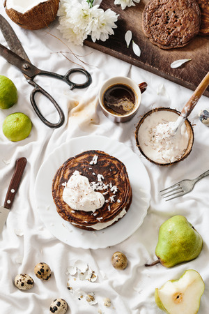 Breakfast scene: Chocolate pancake stack with coconut cream, pear, quail eggs, and coffee Stock Photo