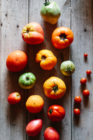 Different varieties of ripe tomatoes.  Vintage wooden table, rustic style Stock Photo