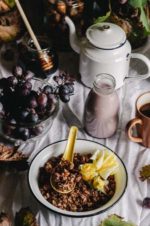 fragrant: A bowl of homemade granola with yellow roses for breakfast - oats, hazelnuts, ground walnuts, honey, and cinnamon. A bottle of walnut milk ready to be poured, grapes, and a cup of freshly brewed coffee. Rustic style