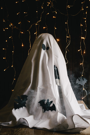 All Hallows Eve. A quirky ghost with a knife, smoke, bats, and fairy lights in the background. Moody atmosphere