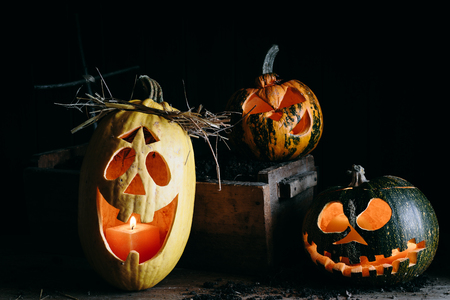Halloween decorations - three carved pumpkins with candles next to a fresh Stock Photo