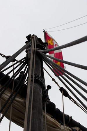 Old Sailing Ship Replica main mast with Columbus flag. photo
