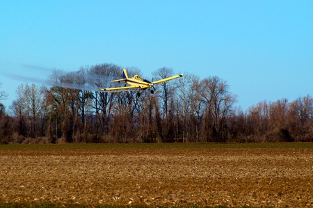 Crop duster at work applying chemicals to field photo