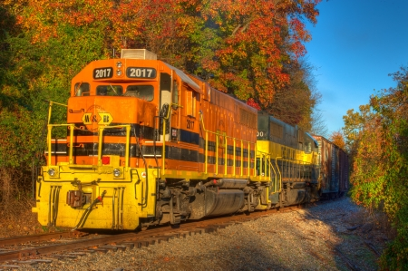 goods train: Freight train locomotive rolling through fall countryside.