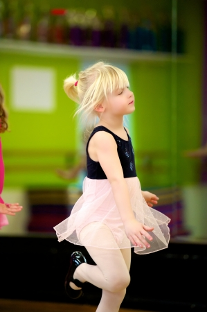 Adorable little girl dancing in ballet class. photo