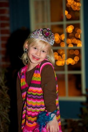 Darling little girl wearing princess crown and earrings.