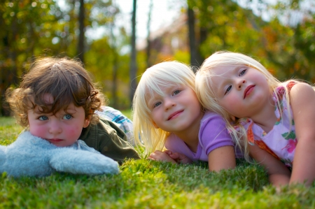 Young children Laying on grass on warm summer afternoon.
