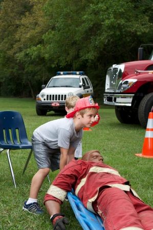Boy learning about fire and rescue in a park. Stock Photo