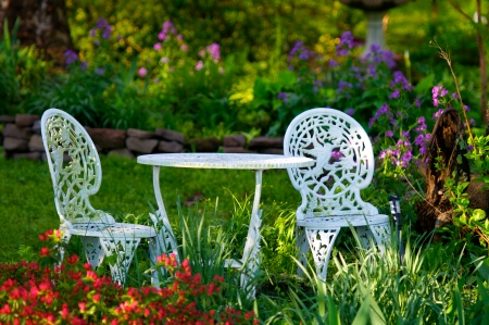A cozy garden getaway in the early morning summer sunshine. Stock Photo