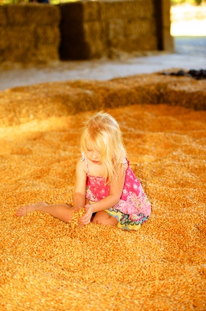 Pretty Young Child Playing in fall harvest Corn Pile.