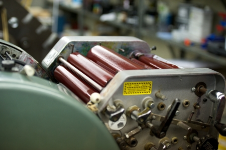 Print rollers on a running press loaded with ink.
