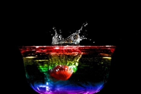 Colorful high speed of a strawberry splashing in colored water.