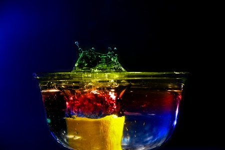 Colorful high speed of a lemon splashing in colored water.