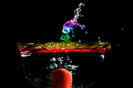 Colorful high speed of a strawberry splashing in colored water