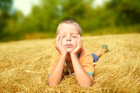 A carefree young boy laying on ground whith eyes shutted photo