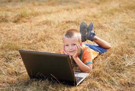 A smiling young boy laying on ground with laptop photo