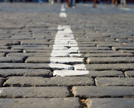 Close-Up of White Stripe On Red Square Block Pavement with blured feet on a distance shot photo