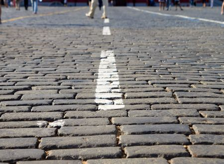 White Stripes On Red Square Block Pavement With Feet on a distance shot photo