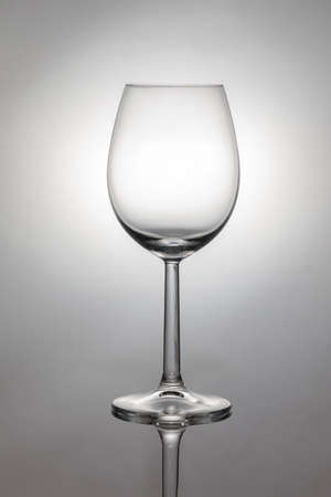 Empty wine glass with black silhouette, reflection and a white backlight