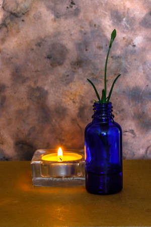 This is a small blue bottle with a lavender cutting and lit at a small candle can be used as a mourning image when someone passed away. Stok Fotoğraf