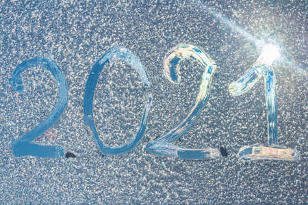 The numbers 2021 traced on a frozen window. Lens flare. Sunlight. Ice texture.