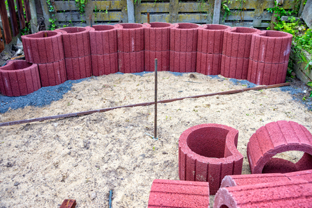 Some Red planting rings lie on a heap in the sand Stock fotó