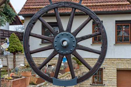 A Wheel of a carriage is hanging on the gate for decoration