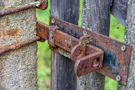 An Old rusted latch that ensures closing of wooden gate Stock Photo