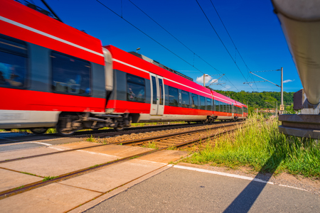 Train drives at high speed past a railroad crossing Reklamní fotografie