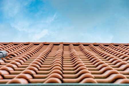 Red roof tiles on a house with blue summer sky