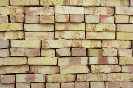 Wall of stacked bricks. New bricks made of clay, manufacturing quality is poor. Stock Photo